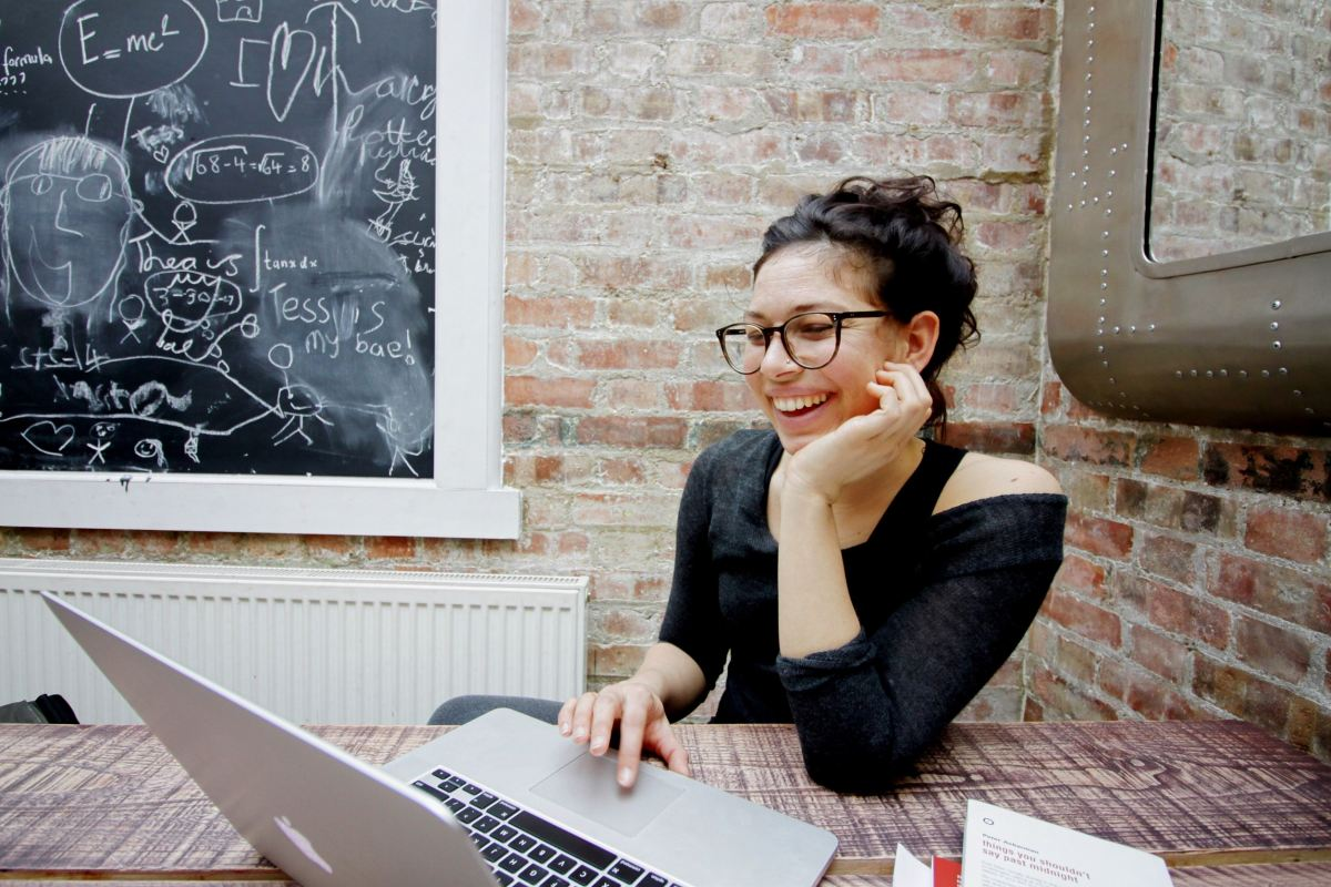 creating a unique brand, girl with computer at desk smiling