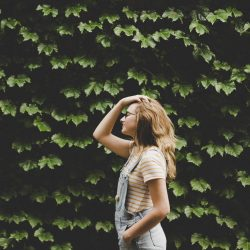 woman standing in front of leaves holding hair