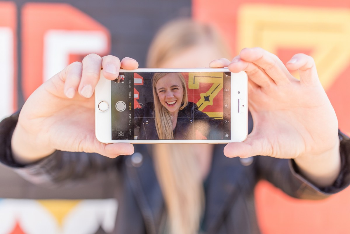 happy girl looking through phone camera