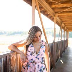 girl looking down walking on bridge