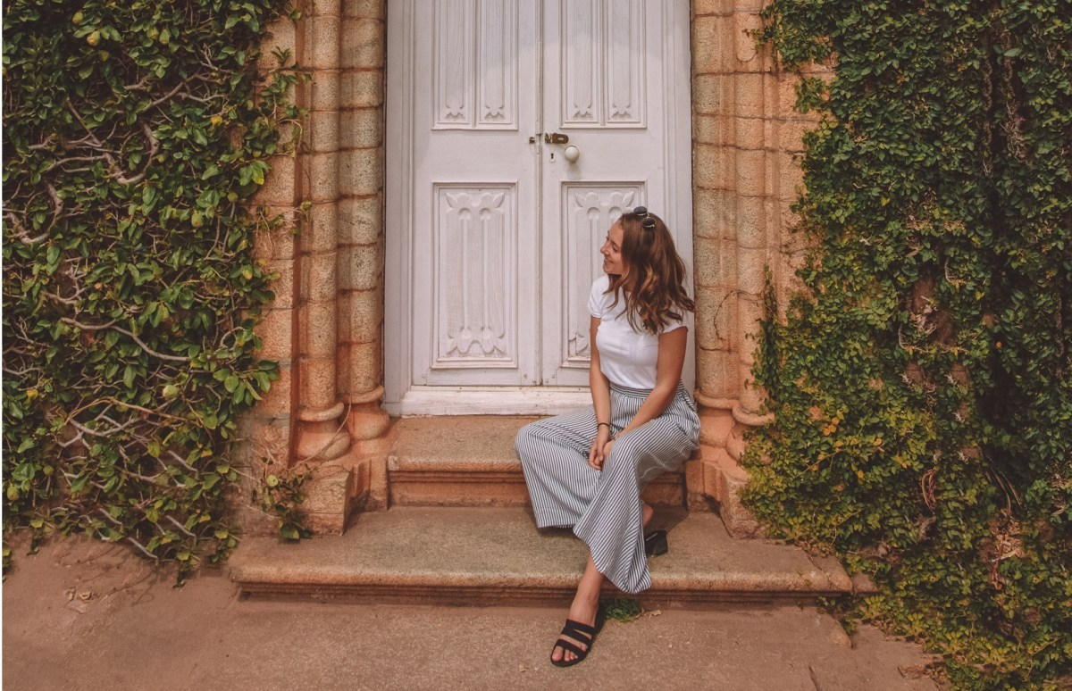 overcoming imposter syndrome, happy woman standing under door